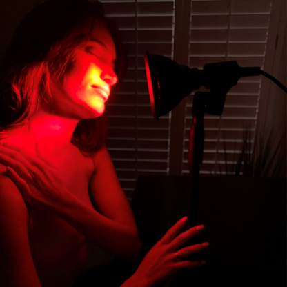 Woman Using TrueLight Energy Scarlet Lux with Stand for Red Light Therapy